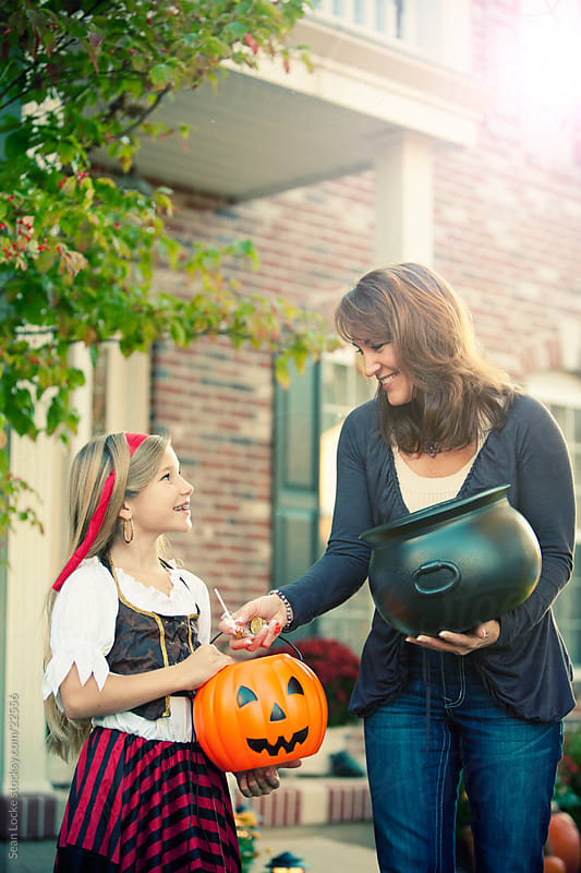 Halloween: Woman Gives Child Candy on Halloween by Sean Locke for Stocksy United