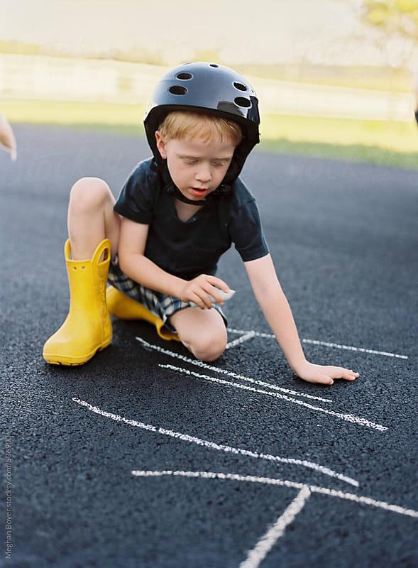 Boy playing with sidewalk chalk outside by Meghan Boyer for Stocksy United