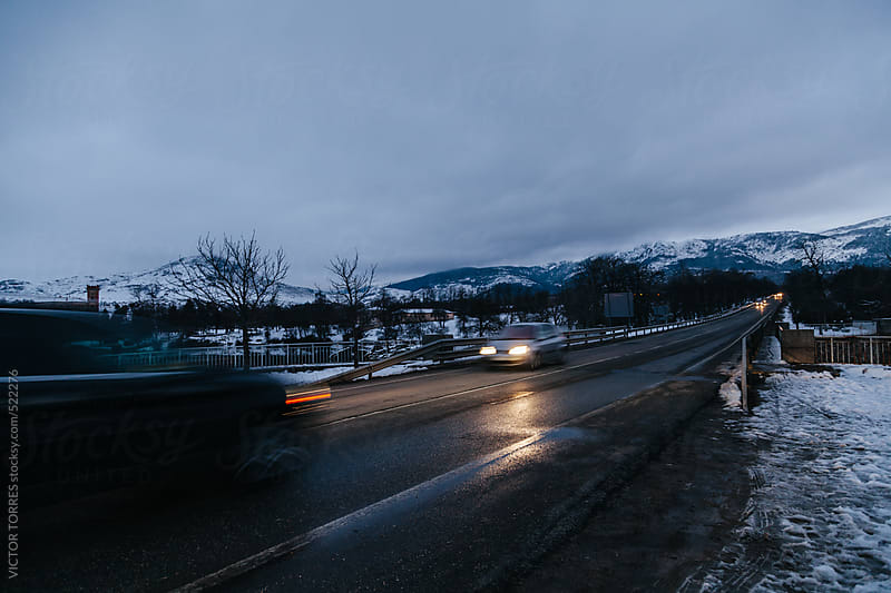 Cars Driving Along a Mountain Snowy Road by Night by VICTOR TORRES for Stocksy United