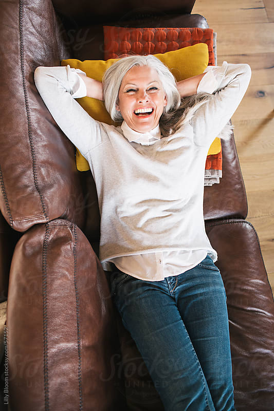 Senior woman lying on her sofa, smiling broadly at the camera. by Lilly Bloom for Stocksy United