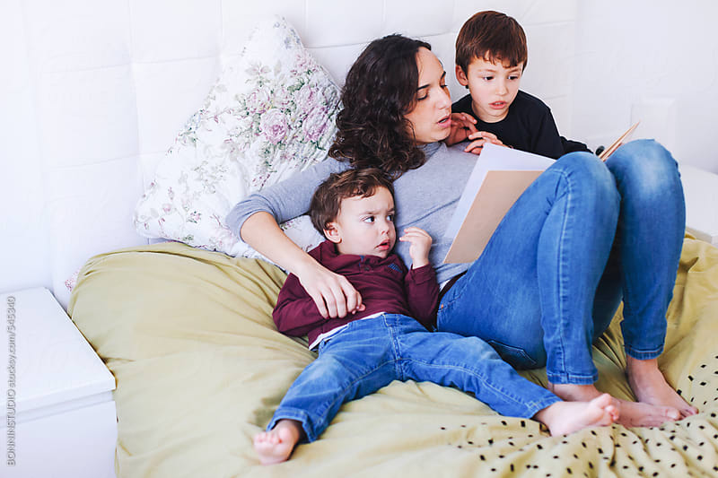 Young mother reading a book to her sons on a bed.  by BONNINSTUDIO for Stocksy United