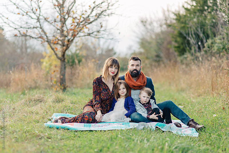 Beautiful and stylish family sitting on a blanket outside by Jakob for Stocksy United