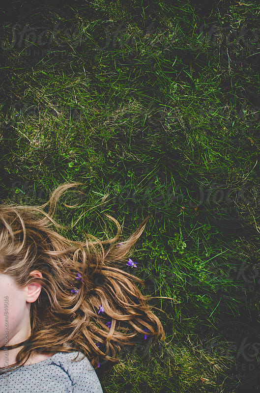 Faceless girl lying in grass by Lindsay Crandall for Stocksy United