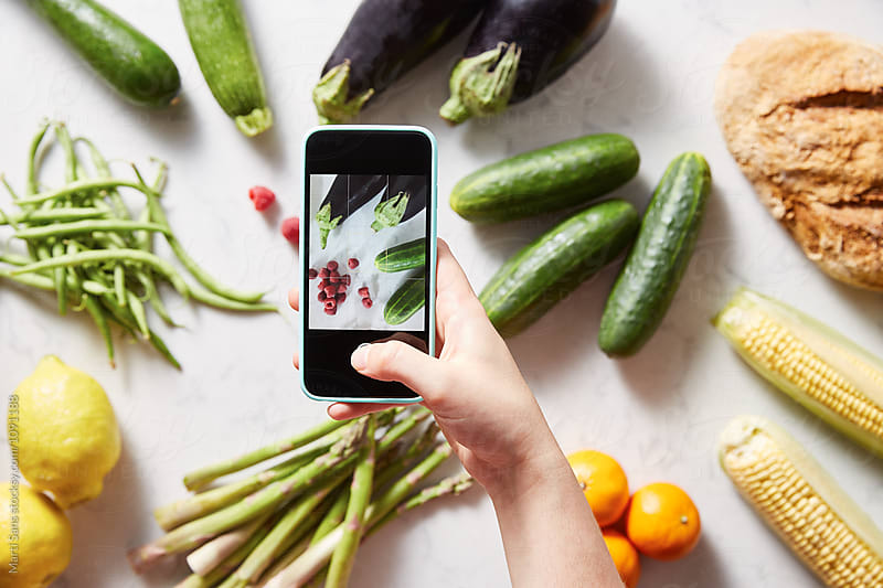 hand making shot of raspberries and vegetables using mobile by Martí Sans for Stocksy United
