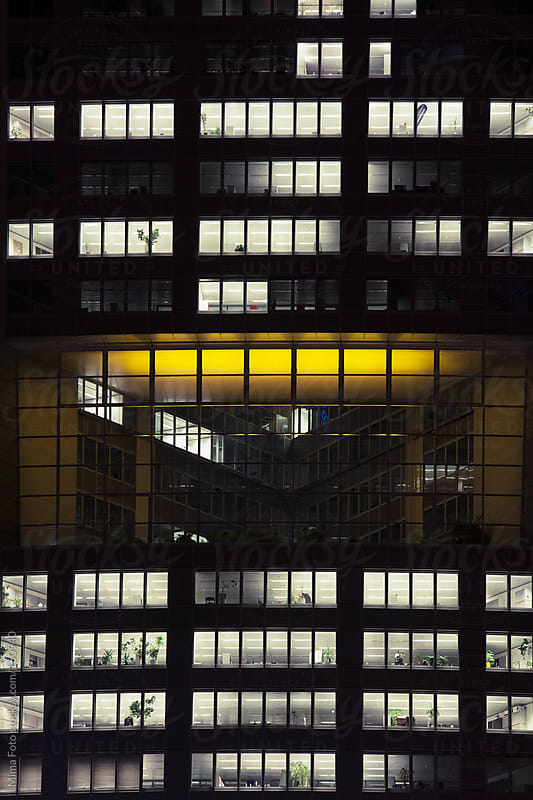 Office skyscraper windows at night by Mima Foto for Stocksy United