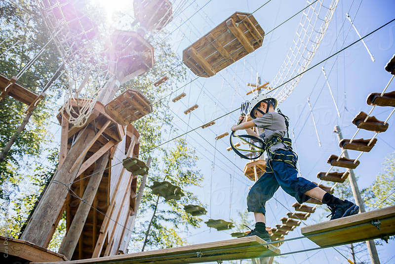 Young boy makes his way across a ropes course by Cara Dolan for Stocksy United
