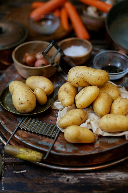Fingerling potatoes in a rustic background. by Darren Muir for Stocksy United