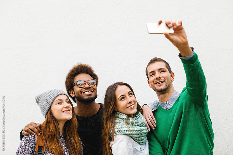 Group of young friends making a selfie with phone on white background. by BONNINSTUDIO for Stocksy United
