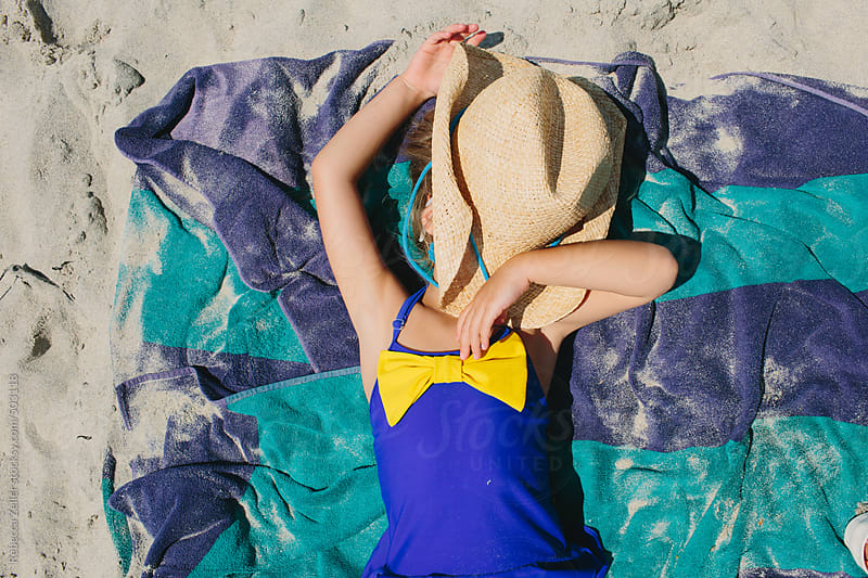 a girl with a cowboy hat over her face is lying on a striped towel at the beach by Rebecca Zeller for Stocksy United