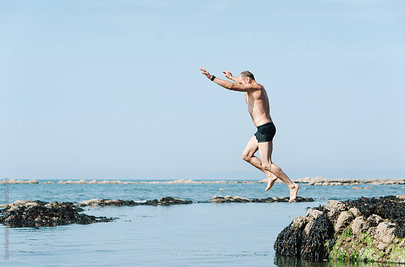Man jumping into the sea from a rock by Suzi Marshall for Stocksy United