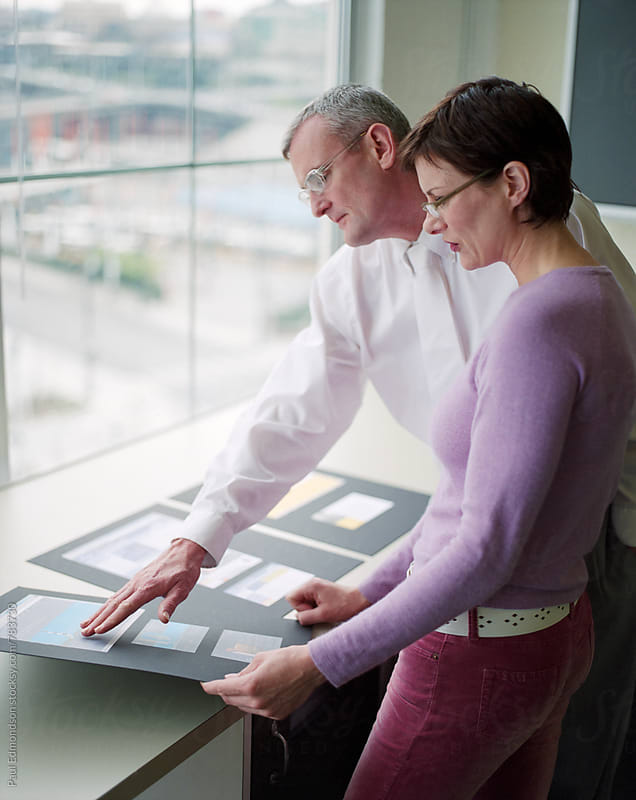 Two marketing executives looking over documents in office by Paul Edmondson for Stocksy United