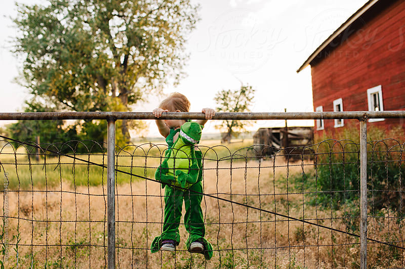 Toddler girl in a dinosaur costume climbing a fence. by Jessica Byrum for Stocksy United