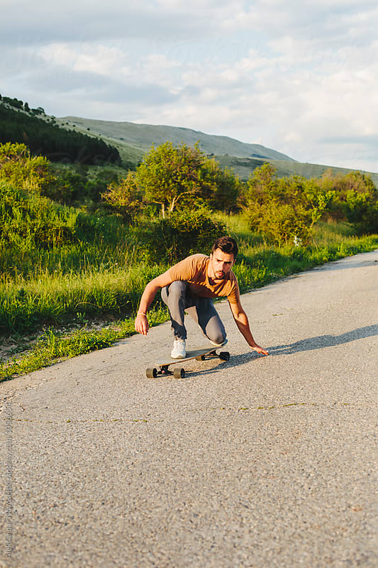 Young man longboarding by Aleksandar Novoselski for Stocksy United