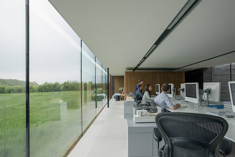 Contemporary office with employees behind monitors at a large table by Paul Phillips for Stocksy United
