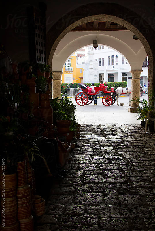 Doorway with horse carriage on background. Cartagena de Indias, Colombia travel by Alejandro Moreno de Carlos for Stocksy United