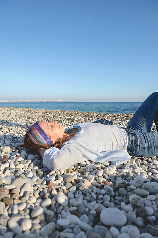 Young woman relaxing on a pebble beach by RG&B Images for Stocksy United