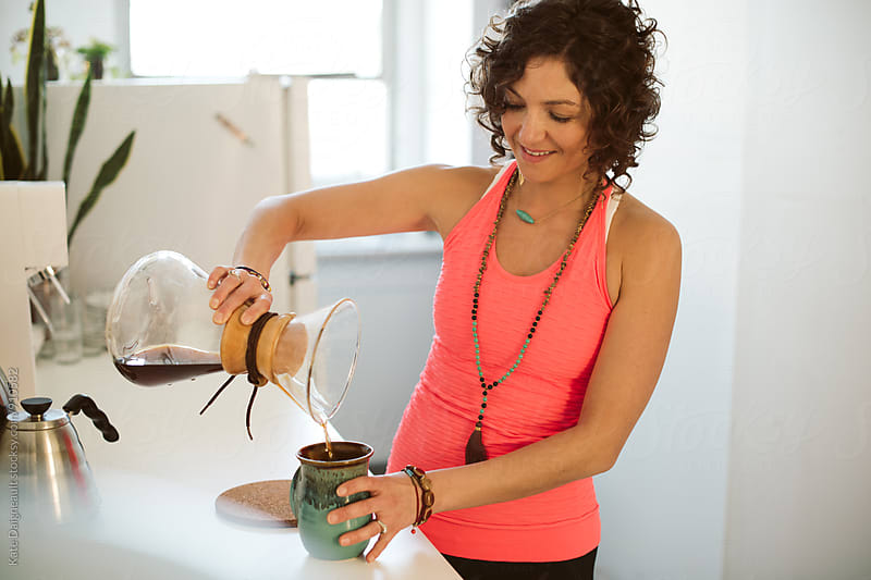 Bohemian woman pours fresh made coffee by Kate Daigneault for Stocksy United