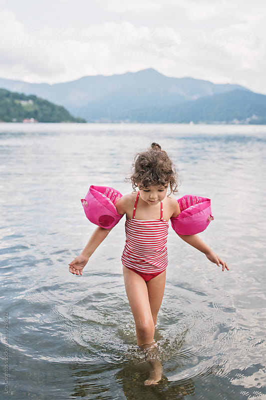 Little girl walking in a lake by Lea Csontos for Stocksy United