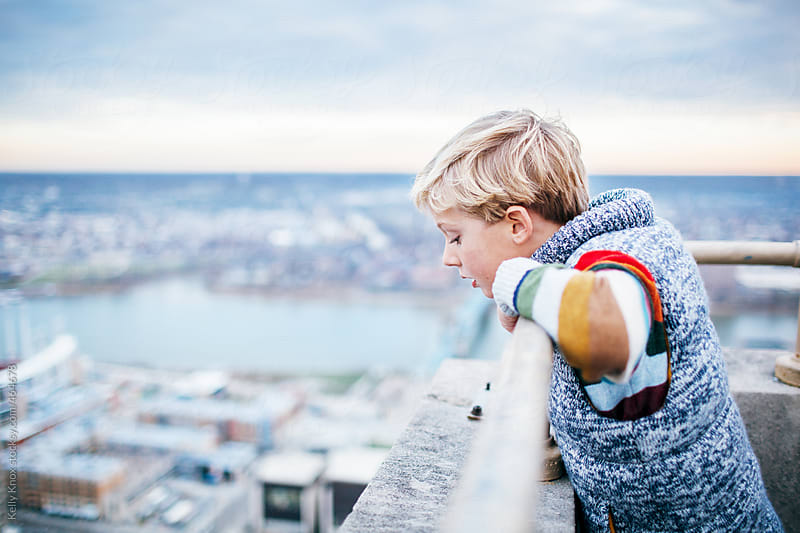 boy on top of a high building looks down at the city below by Kelly Knox for Stocksy United