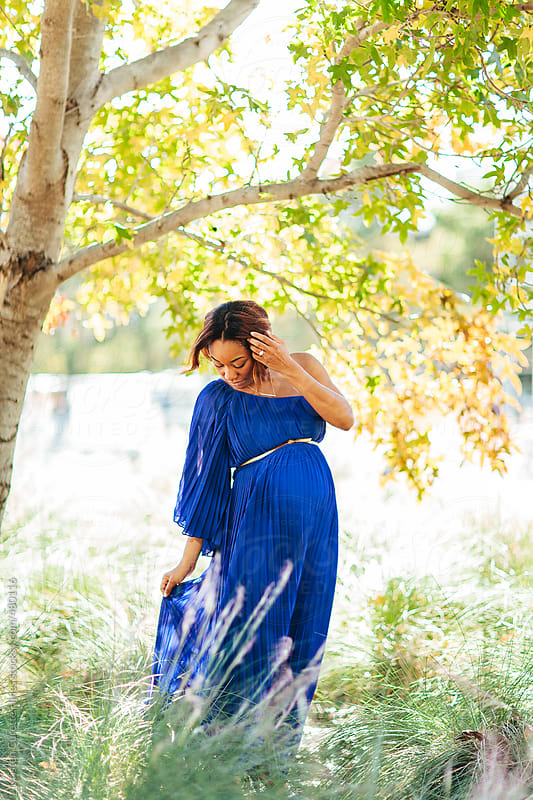 A glowing young pregnant woman enjoying a pretty day in the park by Kristen Curette Hines for Stocksy United