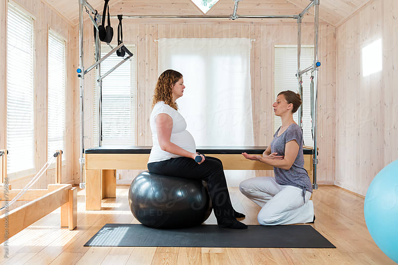 Pilates instruction being given to a pregnant woman whilst seated on a large pilates ball by Paul Phillips for Stocksy United