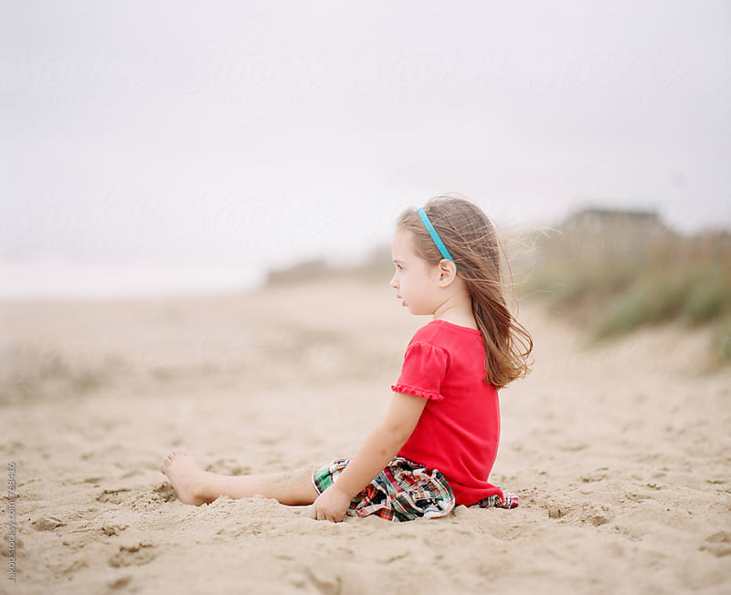 Cute young girl sitting on a beach while looking over an ocean by Jakob for Stocksy United