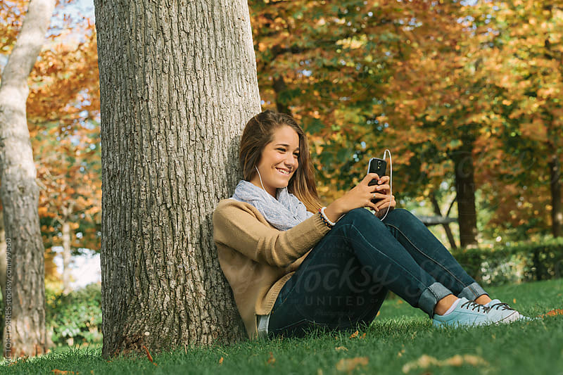Cute Teenager Listening to Music on a Cell Phone in the Park by VICTOR TORRES for Stocksy United
