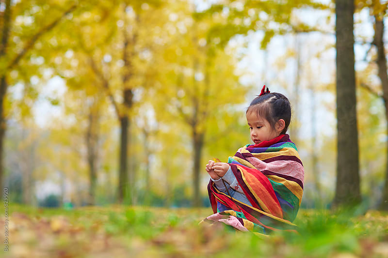 little asian girl having fun in the autumn woods by Bo Bo for Stocksy United