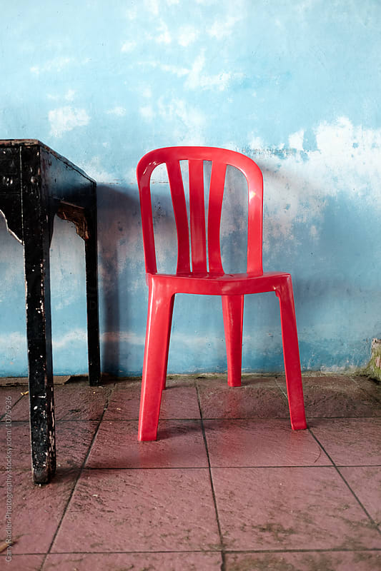 Red Plastic Chair and Wooden Table Oriented Vertically by Gary Radler Photography for Stocksy United