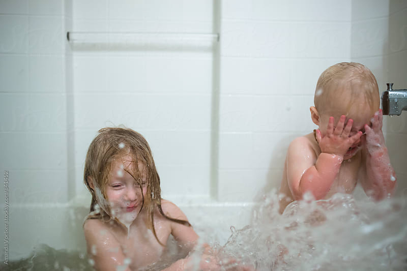 A Young Brother and Sister Splash in the Tub by Amanda Voelker for Stocksy United