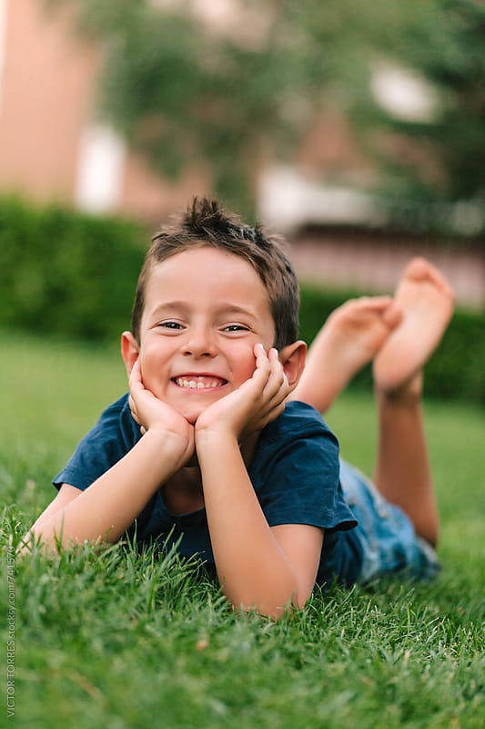 Portrait of an Adorable Boy Lying on Grass by Victor Torres for Stocksy United