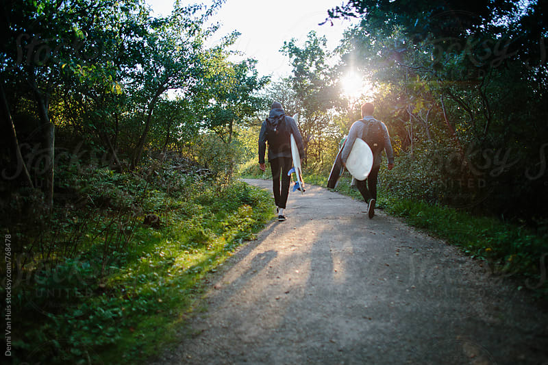 Two friends hike through the forest while holding surfboards by Denni Van Huis for Stocksy United