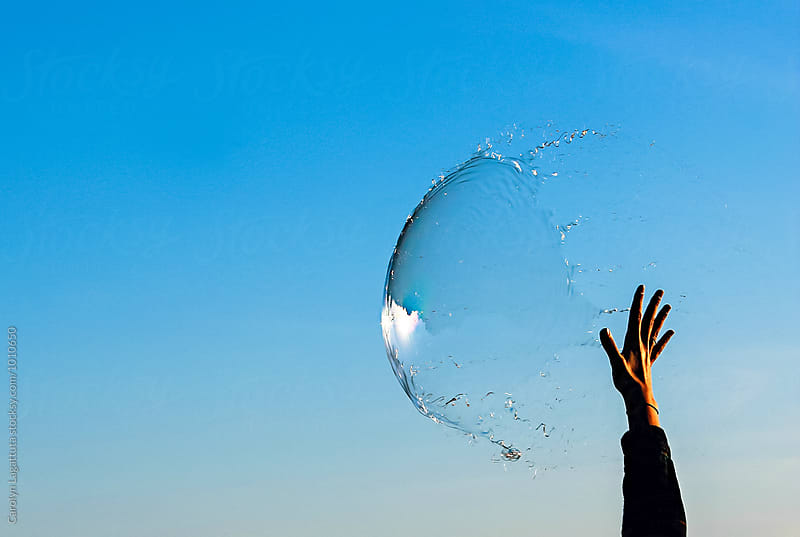 Hand reaching up to pop a big bubble by Carolyn Lagattuta for Stocksy United