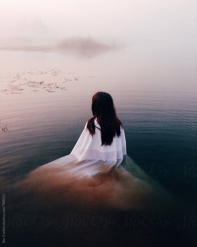 Woman in white dress in lake at sunrise by Bor Cvetko for Stocksy United