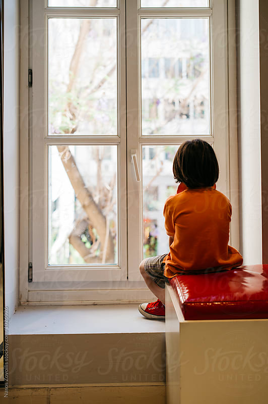 5 year old boy looking outside of a window by Nasos Zovoilis for Stocksy United