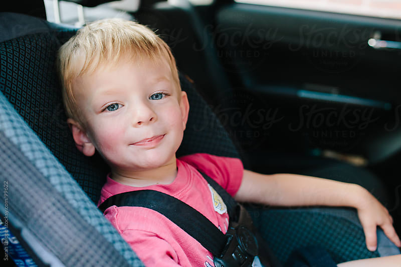 little boy making faces in his carseat by Sarah Lalone for Stocksy United