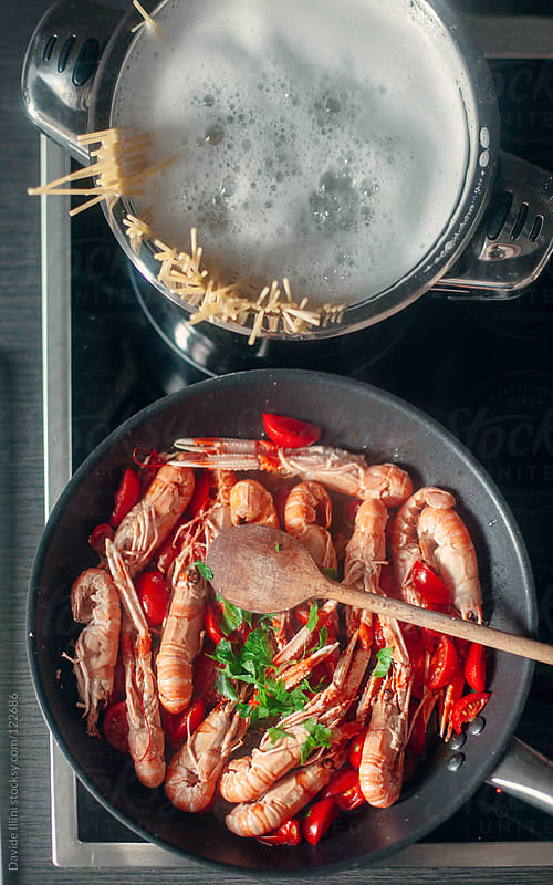 Cooking spaghetti with scampi by Davide Illini for Stocksy United