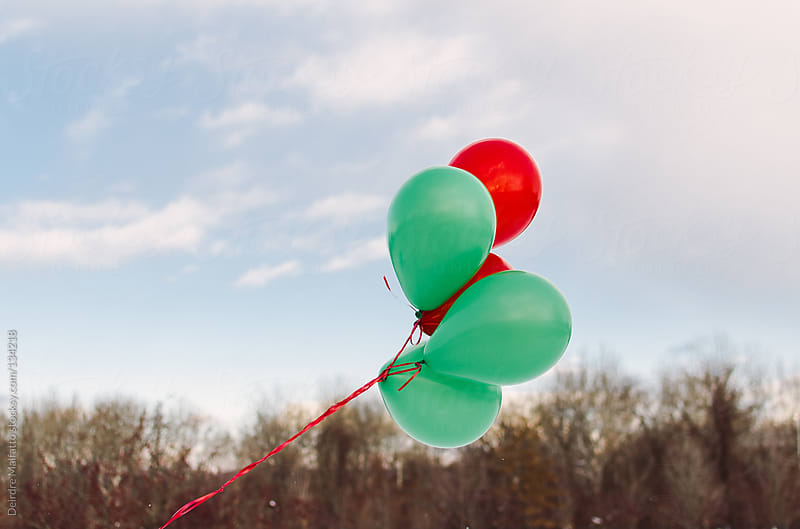 red and green Christmas balloons against a winter landscape by Deirdre Malfatto for Stocksy United
