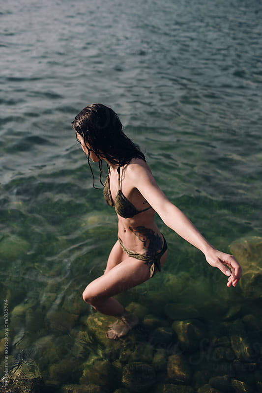 Woman entering the water by michela ravasio for Stocksy United