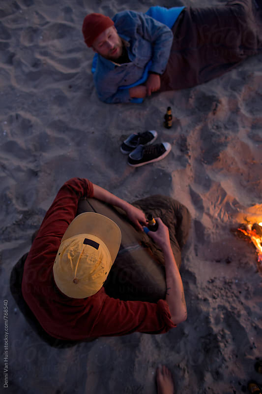 Two friends camping on the beach next to a bonfire by Denni Van Huis for Stocksy United