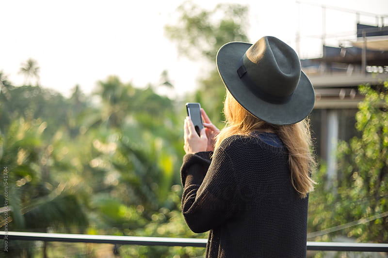 Young woman taking pictures with a smart phone by Jovo Jovanovic for Stocksy United