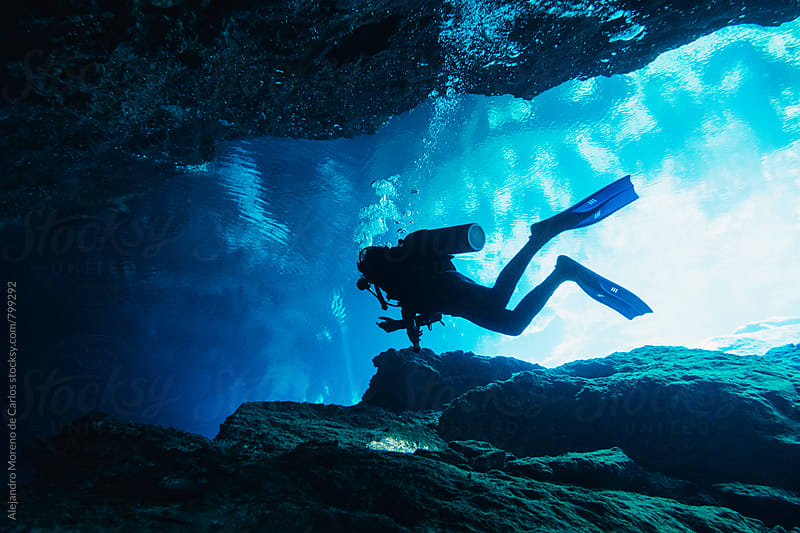 Scuba diver doing cave diving in an underwater cave in a cenote in Yucatán, Mexico by Alejandro Moreno de Carlos for Stocksy United