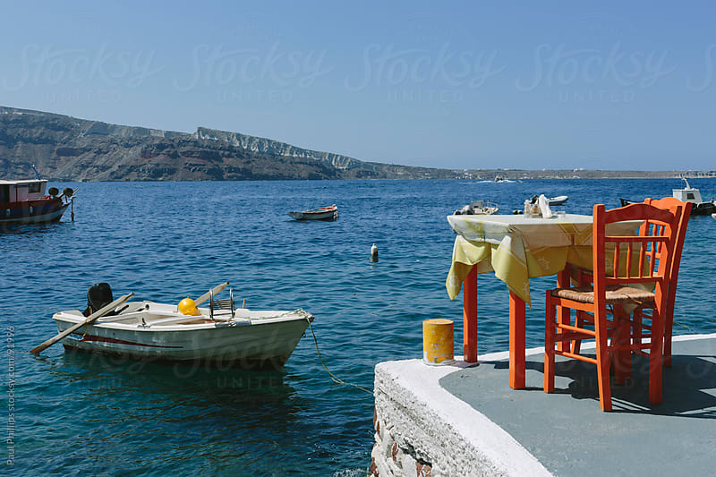 Table and chairs by the bay, Santorini by Paul Phillips for Stocksy United
