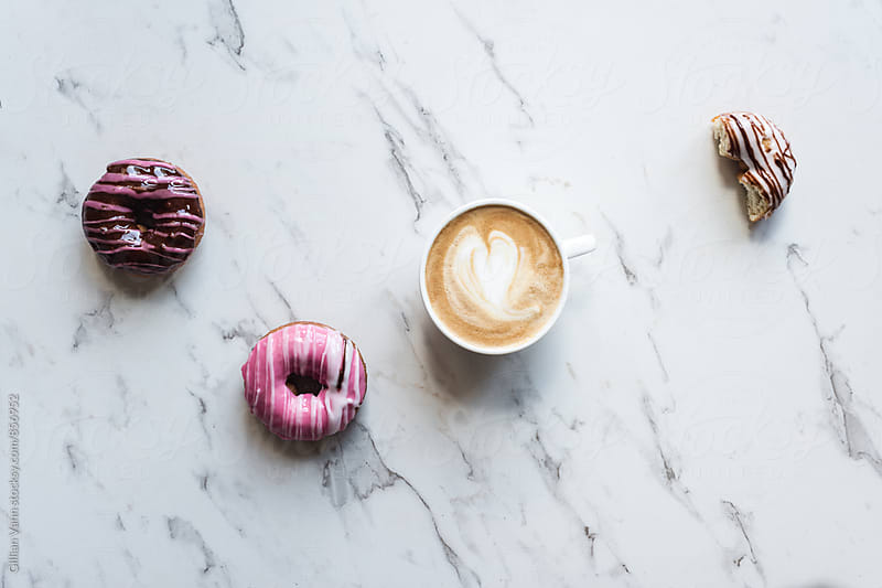 coffee and donuts on a marble background by Gillian Vann for Stocksy United