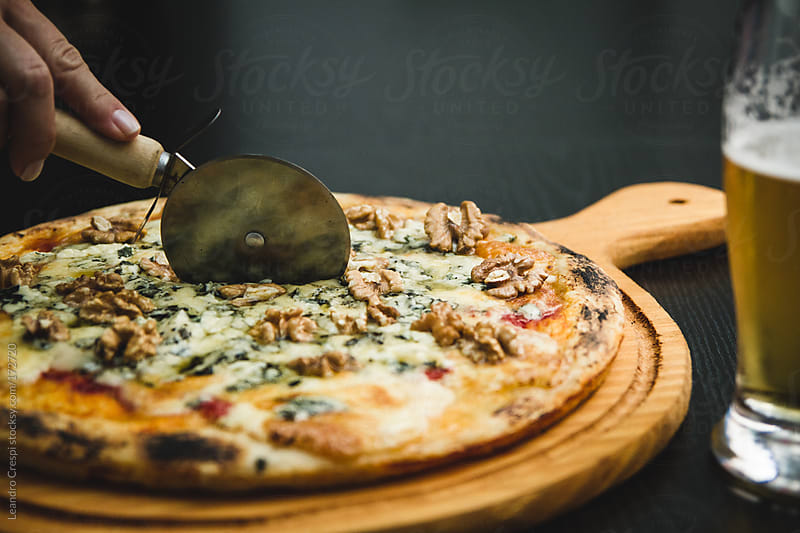 Cutting pizza, roquefort cheese and nuts, beer by Leandro Crespi for Stocksy United