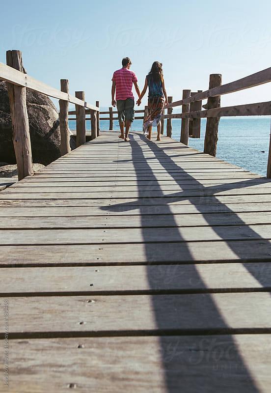 Summer walks - couple walking on wooden pier by Jovo Jovanovic for Stocksy United