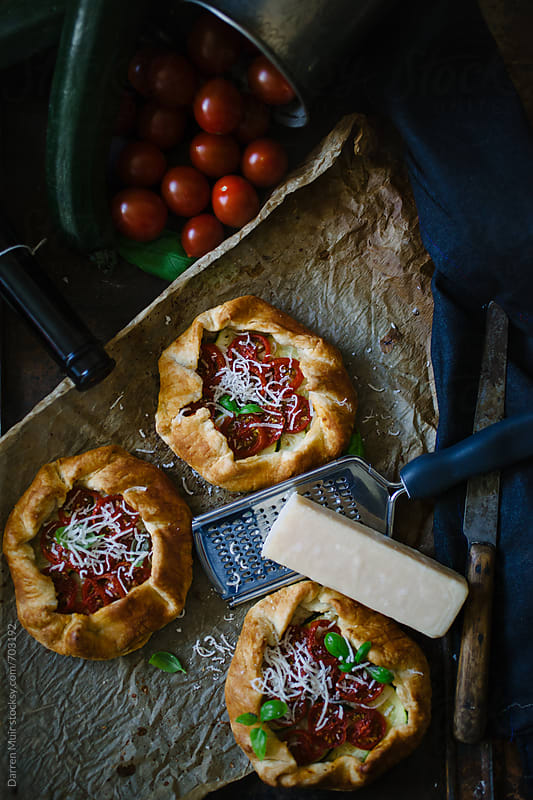 Three tomato and courgette galettes with parmesan. by Darren Muir for Stocksy United