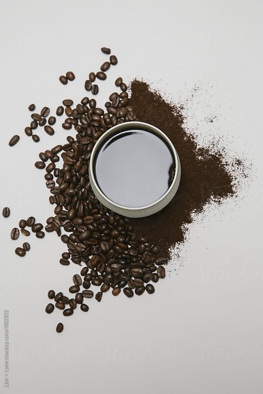 Cup of black coffee next to coffee beans and grains on white background by Lior + Lone for Stocksy United