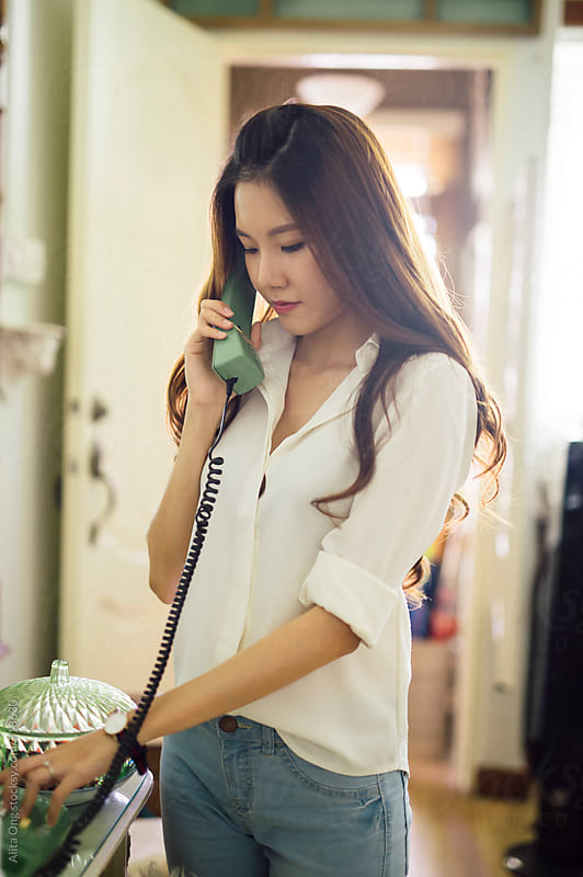 A woman dialling to make phone call by Alita Ong for Stocksy United
