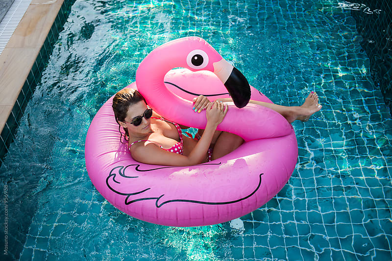Woman in the Pool Floating on a Big Pink Flamingo by Mosuno for Stocksy United